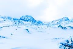 Paisagem nas montanhas neve-tampadas na névoa Fotografia de Stock Royalty Free