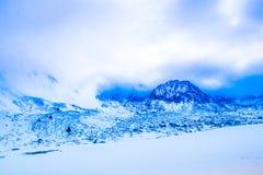 Paisagem nas montanhas neve-tampadas na névoa Fotos de Stock Royalty Free