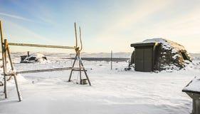 Paisagem nevado bonita de Noruega do norte em setembro com casas de madeira e estruturas étnicas mornas sob a terra fotografia de stock