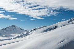 Paisagem nevado da montanha no fundo do céu azul Imagens de Stock