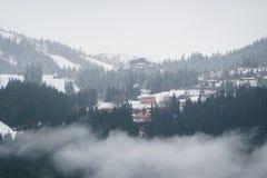 Paisagem norueguesa com as casas escandinavas típicas nas montanhas e a floresta coberta com a neve Cena do inverno foto de stock
