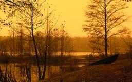 A paisagem nos tons ambarinos com um barco foto de stock royalty free