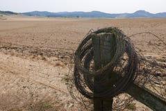 Paisagem ocidental seca com cerca e um rolo do arame farpado imagem de stock royalty free