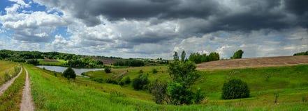 Paisagem panorâmico do verão ventoso nebuloso com estrada secundária à terra e os montes verdes fotografia de stock