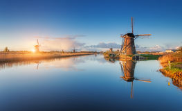 Paisagem rústica com surpresa de moinhos de vento holandeses no nascer do sol Fotografia de Stock