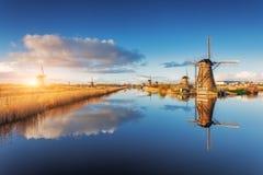 Paisagem rústica com surpresa de moinhos de vento holandeses no nascer do sol Foto de Stock Royalty Free
