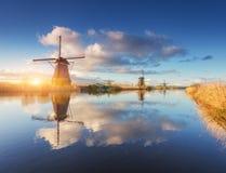 Paisagem rústica com surpresa de moinhos de vento holandeses no nascer do sol Fotografia de Stock Royalty Free