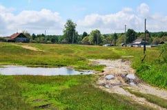 Paisagem rural com estrada de terra, casas e poder foto de stock royalty free