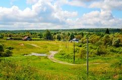 Paisagem rural com estrada de terra, casas e poder fotos de stock