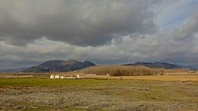 Paisagem rural com exploração agrícola e montanhas de Sierra Nevada no fundo sob nuvens cinzentas escuras foto de stock royalty free