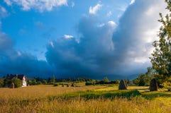 Paisagem rural com monte de feno em um dia ensolarado do verão Paisagem rural da montanha com nuvens de tempestade foto de stock