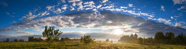 Paisagem rural do verão com estrada, um prado, a floresta e a névoa, panor Foto de Stock