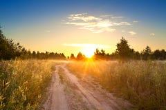 Paisagem rural do verão com nascer do sol, névoa e a estrada Foto de Stock