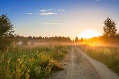 Paisagem rural do verão com nascer do sol, névoa e a estrada Imagem de Stock