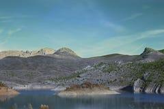 Paisagem seca da montanha com o lago em tons mornos com mal alguma vegetação foto de stock