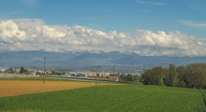 Paisagem surpreendente com campo, as montanhas e as nuvens verdes Fotografia de Stock