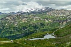 Paisagem surpreendente com estrada da montanha, lago e picos de montanha Áustria Parque nacional de Tauern Imagens de Stock Royalty Free