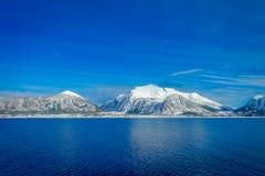 Paisagem surpreendente das cenas litorais da montanha enorme cobertas com a neve em Hurtigruten durante a viagem em um céu azul Fotografia de Stock Royalty Free
