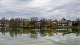 A paisagem tranquilo com lago, casas, o céu nebuloso, e as árvores refletiu simetricamente na água Nyiregyhaza, Hungria imagem de stock