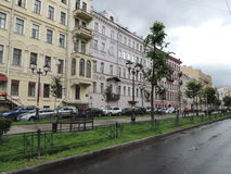 Paisagem urbana após a rua da chuva com construção e carros Imagens de Stock