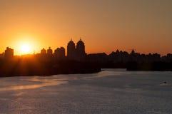 Paisagem urbana durante o por do sol Uma grande extensão da água Fotografia de Stock Royalty Free