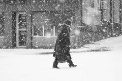 Paisagem urbana nevando com a mulher que passa perto Fotografia de Stock