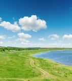 Paisagem verde com estrada e lagoa sob o céu azul fotografia de stock royalty free