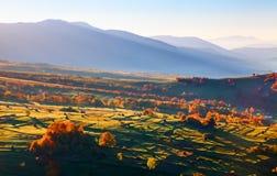 Paisagens maravilhosas com as cidades com campos e monte de feno Árvores de fruto com folhas coloridas Montanhas altas imagens de stock royalty free