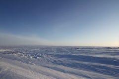 Paisaje ártico del invierno blanco con nieve que sopla en la tierra un cielo sin fin azul Imagen de archivo