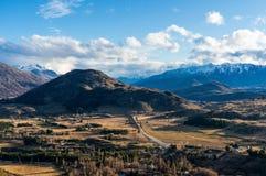 Paisaje épico del valle de la montaña Silueta del hombre de negocios Cowering Imagenes de archivo