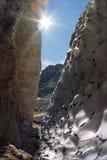 Paisaje abstracto soleado hermoso de la montaña rocosa con una hendidura entre la nieve y la roca Imagen de archivo libre de regalías