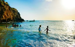 Paisaje, adolescencias y niños del océano de Cabo Verde jugando en el agua, playa volcánica negra Imagen de archivo