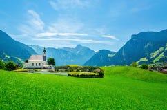 Paisaje alpino con las montañas típicas del austriaco de la iglesia Imágenes de archivo libres de regalías