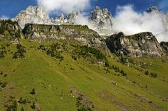 Paisaje alpino con los prados y los picos rocosos Foto de archivo libre de regalías