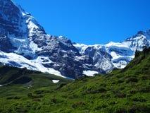 Paisaje alpino de la gama de montañas cerca del pueblo de GRINDELWALD en las MONTAÑAS suizas de la belleza en SUIZA Imagen de archivo libre de regalías