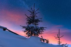 Paisaje alpino del invierno colorido en la noche con el cielo estrellado y el resplandor de la puesta del sol imagenes de archivo