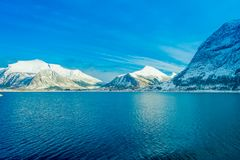 Paisaje asombroso de las escenas costeras de la montaña enorme cubiertas con nieve en Hurtigruten durante viaje en un cielo azul Imagenes de archivo