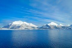 Paisaje asombroso de las escenas costeras de la montaña enorme cubiertas con nieve en Hurtigruten durante viaje en un cielo azul Imágenes de archivo libres de regalías