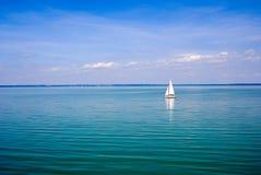 Paisaje azul con el barco de vela fotos de archivo