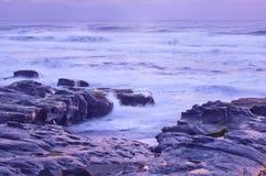 Paisaje cambiante del paisaje marino del océano en la playa rocosa con tonalidad púrpura Imagenes de archivo