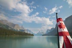 Paisaje canadiense con las montañas, el lago Maligne y la bandera albert Imágenes de archivo libres de regalías