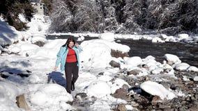 Paisaje colorido del invierno con una muchacha que camina a lo largo de un lago de la montaña Hermosa vista del invierno idílico  almacen de metraje de vídeo