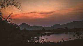 Paisaje con anaranjado y en las siluetas de la puesta del sol de montañas fotografía de archivo libre de regalías