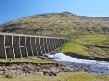 Paisaje con el agua de lluvia de Vestmanna que cosecha el aliviadero de la presa y del agua fotos de archivo libres de regalías