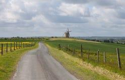 Paisaje con el camino y el molino de viento Imagenes de archivo