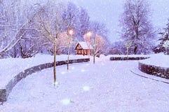 Paisaje con la casa sola iluminada - opinión de la noche del invierno del paisaje del invierno con los copos de nieve Foto de archivo libre de regalías