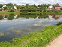 Paisaje con las cabañas y el lago 2 Imágenes de archivo libres de regalías