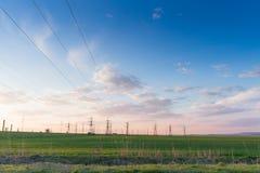 Paisaje con las líneas eléctricas de alto voltaje Distributio de la electricidad Imagen de archivo libre de regalías