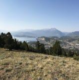 Paisaje con las montañas en la distancia y el pequeño pueblo imagenes de archivo