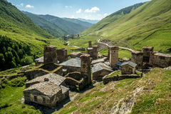 Paisaje con las torres y las casas de piedra tradicionales viejas en el pueblo rural Ushguli Valle de la montaña con los pastos v Imagen de archivo